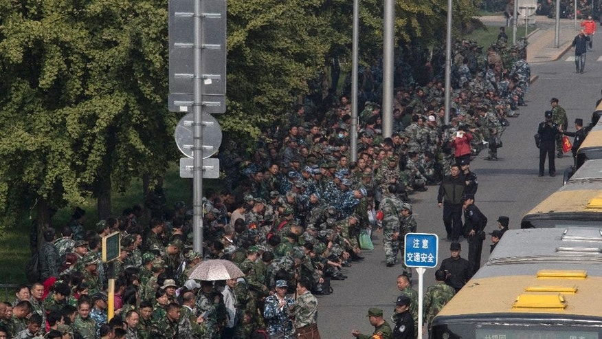Hundreds of protesters in green fatigues gather outside the Chinese Ministry of National Defense to protest in Beijing, China, Tuesday, Oct. 11, 2016. China's military is undergoing a large-scale modernization and cutting hundreds of thousands of soldiers from the ranks. More than 1,000 protesters walked and chanted Tuesday, the latest apparent demonstration by soldiers during a wide-ranging campaign to modernize and downsize the military. (AP Photo/Ng Han Guan)