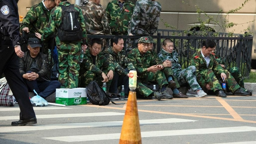 Protesters in green fatigues gather outside the Chinese Ministry of National Defense in Beijing, China, Tuesday, Oct. 11, 2016. More than 1,000 protesters walked and chanted Tuesday, the latest apparent demonstration by soldiers during a wide-ranging campaign to modernize and downsize the military. (AP Photo/Ng Han Guan)