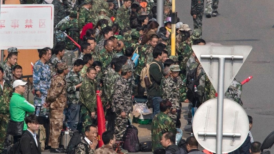 Soldier protesters in green fatigues gather outside the Chinese Ministry of National Defense in Beijing, China, Tuesday, Oct. 11, 2016. More than 1,000 protesters walked and chanted Tuesday, the latest apparent demonstration by soldiers during a wide-ranging campaign to modernize and downsize the military. (AP Photo/Ng Han Guan)