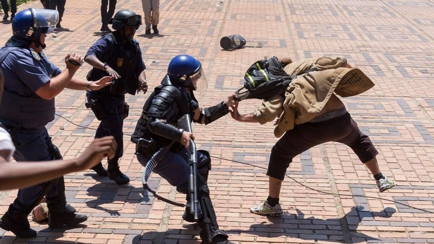 A policeman clashes with a student on the University of the Witwatersrand campus in Johannesburg, South Africa, on Monday, Oct. 10, 2016. Tear gas and water cannon were fired as hundreds of students protested at the university amid a bitter national dispute with university managers and the government over demonstrators' demands for free education. (AP Photo/Yeshiel Panchia)