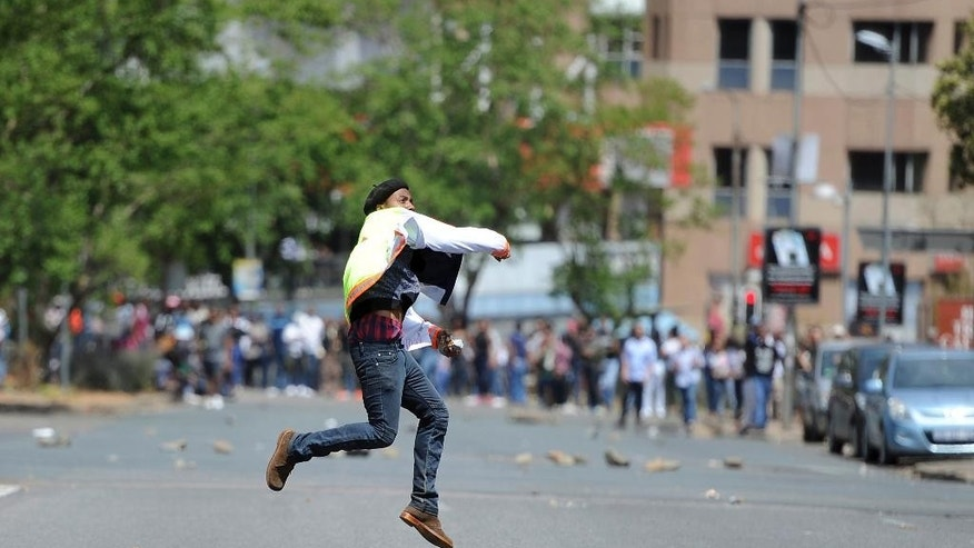 A student hurls a stone off the University of the Witwatersrand campus in Johannesburg South Africa on Monday, Oct. 10, 2016. Tear gas and water cannon were fired as hundreds of students protested at the university amid a bitter national dispute with university managers and the government over demonstrators' demands for free education. (AP Photo)