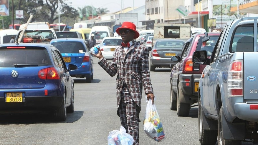 In this Friday, Sept. 30, 2016 photo, Farai Mushayademo, a street vendor, sells water and potato chips to motorists in Harare, Zimbabwe. In his three-piece suit, matching hat and bow tie, Mushayademo could easily pass for a celebrity musician — if only his job didn't involve dodging cars at a busy intersection in Zimbabwe's capital, Harare, selling bottled water and potato chips to passing motorists. Massive joblessness in this once-prosperous southern African country has forced many to flood the streets, where they hawk anything from medicines to car parts. A good gimmick can help a vendor stand out from the crowd. (AP Photo/Tsvangirayi Mukwazhi)