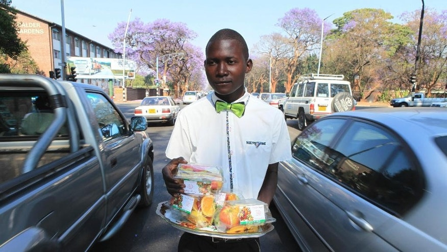 In this Friday, Sept. 30, 2016 photo, Kiziti Gezi, a street vendor, walks through cars as he sells neatly packed fruits to motorists in Harare, Zimbabwe. In his white shirt and bow tie Gezi could easily pass for a waiter - if only his job didn't involve dodging cars at a busy intersection. Massive joblessness in this once-prosperous southern African country has forced many to flood the streets, where they hawk anything from medicines to car parts. A good gimmick can help a vendor stand out from the crowd. (AP Photo/Tsvangirayi Mukwazhi)
