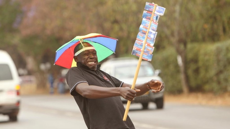 "In this Monday, Oct. 3, 2016 photo, Gilbert Mundicha, a street vendor, dances while selling mobile phone airtime vouchers to motorists in a wealthy multi-racial suburbs in Harare, Zimbabwe. ""My antics are meant to cultivate a personal relationship with customers,"" said Mundicha, who dances, makes military salutes and greets nearly every passing motorist while mimicking what he described as a ""British accent."" Massive joblessness in this once-prosperous southern African country has forced many to flood the streets, where they hawk anything from medicines to car parts. A good gimmick can help a vendor stand out from the crowd. (AP Photo/Tsvangirayi Mukwazhi)"