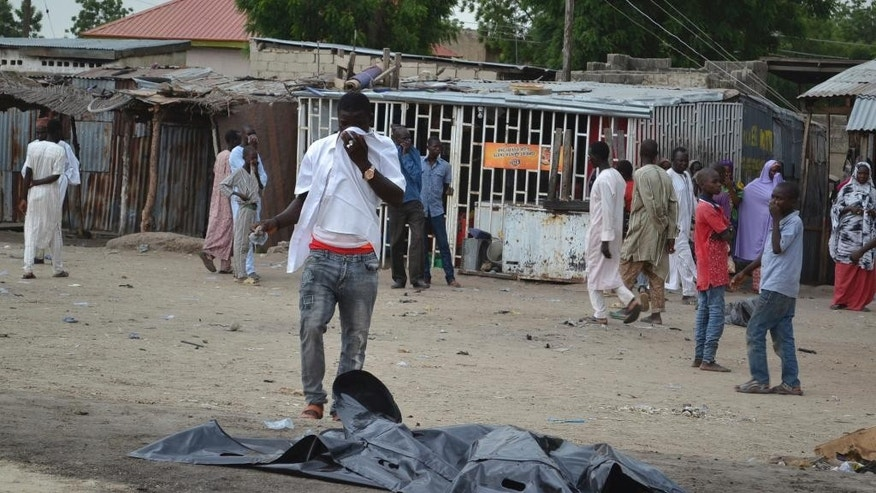 A body lays covered at the scene after a car bomb explosion in Maiduguri, Nigeria, Wednesday, Oct. 12, 2016.  The explosion seemed to target a taxi filled with passengers in northeast Nigeria on Wednesday, in the deadliest bombing to hit the area's largest city in several months, officials and witnesses said. (AP Photo/Jossy Ola)