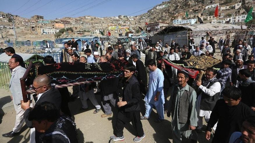 Afghan men carry the coffin of a relative who died in a militant attack at a Shiite shrine in Kabul, Afghanistan, Wednesday, Oct. 12, 2016. An Afghan official says several people including a policeman are dead after a militant attack on a Shiite shrine in the capital Kabul late Tuesday. Sediq Sediqqi, the interior ministry's spokesman said Wednesday that another 62 people, including 12 policemen were wounded in the attack. (AP Photos/Rahmat Gul)