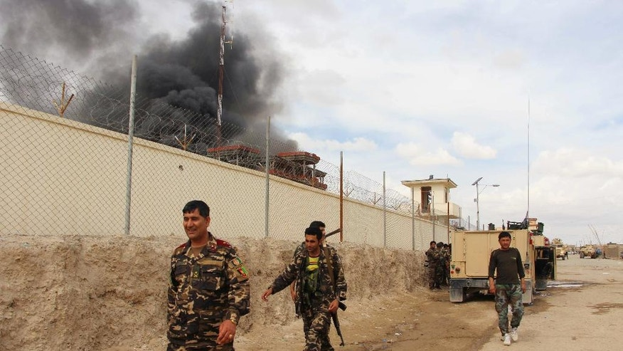 FILE -- In this March 9, 2016 file photo, smoke rises from a building, where Taliban insurgents hide during a fire fight with Afghan security forces, in Helmand province, Afghanistan. For the past month, the Taliban have held control over most of Afghanistan's Helmand province, where the majority of the world's opium is grown -- and as insurgent attacks intensify around the provincial capital, residents are blaming rampant government corruption for the rising militant threat. At an international aid conference in Brussels that closed Wednesday, Oct. 5, 2016, Afghanistan's leaders pledged to clamp down on graft, but corrupt officials have hollowed out national security forces and are alienating local populations. (AP Photo, File)