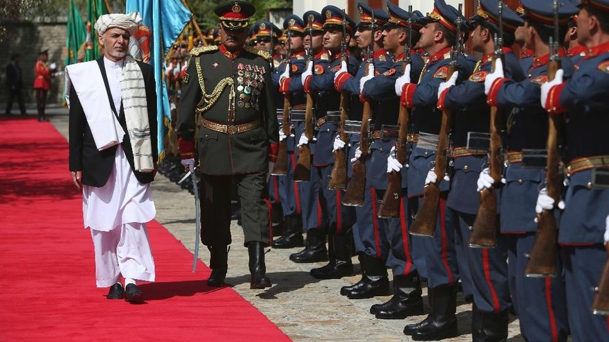 In this Sept. 29, 2016, photo, Afghan President Ashraf Ghani, left, inspects an honor guard at the presidential palace in Kabul, Afghanistan. For the past month, the Taliban have held control over most of Afghanistan's Helmand province, where the majority of the world's opium is grown -- and as insurgent attacks intensify around the provincial capital, residents are blaming rampant government corruption for the rising militant threat. At an international aid conference in Brussels that closed Wednesday, Oct. 5, 2016, Afghanistan's leaders pledged to clamp down on graft, but corrupt officials have hollowed out national security forces and are alienating local populations. (AP Photo/Rahmat Gul)