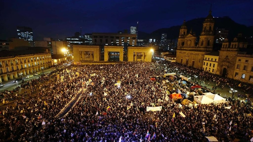 People gather at Bolivar's square during a peace march in Bogota, Colombia, Wednesday, Oct. 12, 2016. Thousands of rural farmers, indigenous activists and students marched in cities across Colombia to demand a peace deal between the government an leftist rebels no be scuttled. (AP Photo/Fernando Vergara)