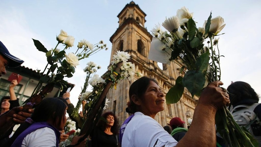 A woman holds flowers as she attends a peace march in Bogota, Colombia, Wednesday, Oct. 12, 2016. Thousands of rural farmers, indigenous activists and students marched in cities across Colombia to demand a peace deal between the government an leftist rebels no be scuttled. (AP Photo/Fernando Vergara)