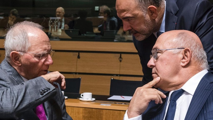 German Finance Minister Wolfgang Schauble, left, talks with Franch Finance Minister Michel Sapin, right, and European Commissioner for Economic Affairs, Taxation and Customs Pierre Moscovici during an EU finance ministers meeting at the EU Council in Luxembourg Tuesday, Oct. 11, 2016. (AP Photo/Geert Vanden Wijngaert)