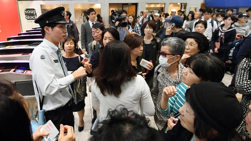A station attendant, left, responds to passengers at a station in Tokyo after train services are suspended Wednesday, Oct. 12, 2016. An extensive blackout struck Tokyo on Wednesday, affecting government offices and halting trains in the Japanese capital just before the evening rush hour. (Akiko Matsushita/Kyodo News via AP)