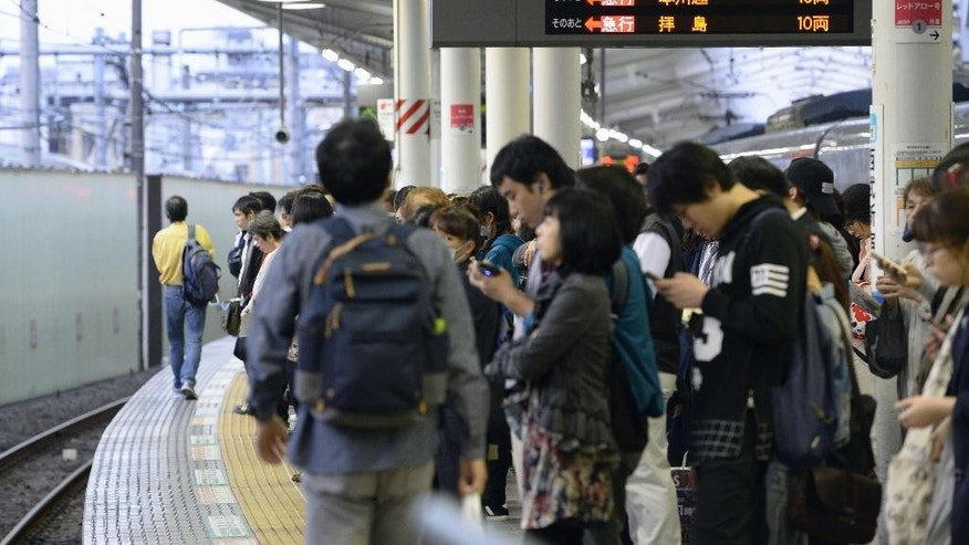 Passengers wait for a train at a station in Tokyo's Shinjuku district after train services are suspended Wednesday, Oct. 12, 2016. An extensive blackout struck Tokyo on Wednesday, affecting government offices and halting trains in the Japanese capital just before the evening rush hour. (Akiko Matsushita/Kyodo News via AP)