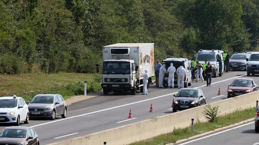 FILE - In this Aug. 27, 2015 file photo police stand near a  truck that  stands on the shoulder of the highway A4 near Parndorf south of Vienna, Austria. Various murder and smuggling charges will be recommended against one Afghan and seven Bulgarian suspects for the Aug. 2015 deaths of 71 migrants who suffocated in the back of a refrigerated truck, Hungarian police said Wednesday, Oct. 12, 2016. (AP Photo/Ronald Zak)