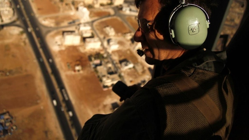 """In this Sept. 27, 2016 photo, Robert Bewley uses his radio headset to guide helicopter pilots from the Jordanian air force to an archaeological site in Jordan. Bewley and his colleague David Kennedy have spent the past 19 years in an ongoing project documenting from the air archaeological sites around Jordan. Since, they've revealed from the air mysterious rock structures in the bleak eastern desert – and witnessed """"catastrophic"""" urban sprawl destroying and threatening sites across the kingdom. (AP Photo/Sam McNeil)"""