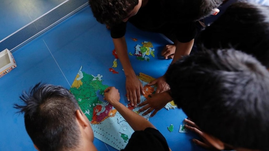 Migrant children make a puzzle, depicting the map of Europe, at a new reception center for unaccompanied minors in Athens, Tuesday, Oct. 11, 2016. The Balkan route, used by nearly 1 million refugees and migrants last year to cross to mainland Europe, was closed last March and over 60,000 people are stranded in Greece. (AP Photo/Thanassis Stavrakis)