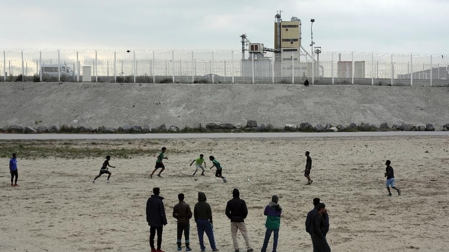 Migrants play soccer in a makeshift migrants camp near Calais, France, Wednesday, Oct. 12, 2016. Charities working with refugees and migrants living in a slum-like camp in northern France objected Tuesday to the government's plan to dismantle the site and disperse the occupants, saying French authorities should not act in haste. (AP Photo/Thibault Camus)