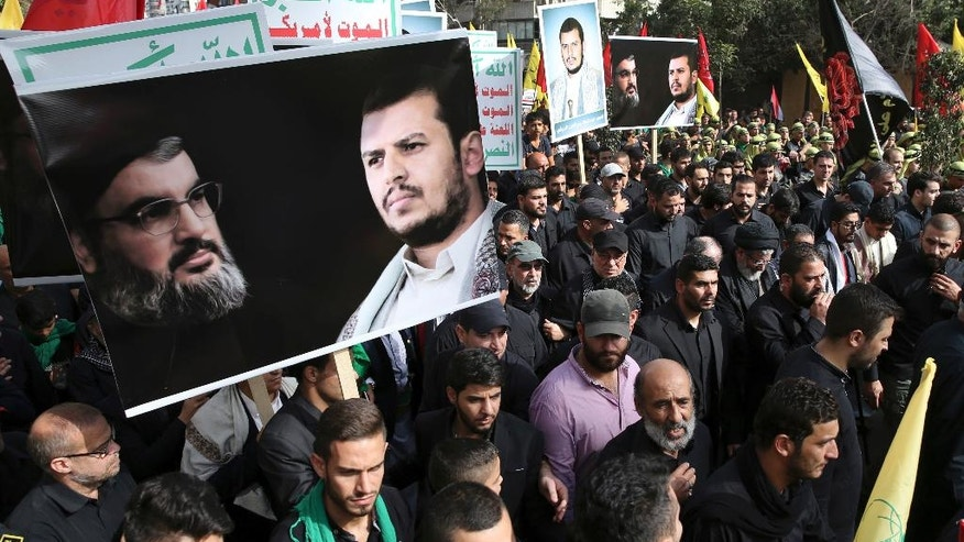 """Lebanese Shiite supporters of the Iranian-backed Hezbollah group, hold portraits of Hezbollah leader Sayyed Hassan Nasrallah and Abdul-Malik al-Houthi, the leader of the Shiite Yemeni rebels, as they march during the holy day of Ashoura, in a southern suburb of Beirut, Lebanon, Wednesday, Oct. 12, 2016. Lebanese Shiites mark Ashoura, the tenth day of the Islamic month of Muharram, to commemorate the Battle of Karbala in the 7th century when Imam Hussein, a grandson of Prophet Muhammad, was killed in present-day Iraq. The Arabic words in background read:""""God is great, Death for America."""" (AP Photo/Hussein Malla)"""