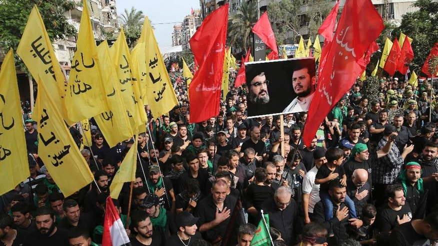 Lebanese Shiite supporters of the Iranian-backed Hezbollah group, hold portraits of Hezbollah leader Sayyed Hassan Nasrallah and Abdul-Malik al-Houthi, the leader of the Shiite Yemeni rebels, as they march during the holy day of Ashoura, in a southern suburb of Beirut, Lebanon, Wednesday, Oct. 12, 2016. Lebanese Shiites mark Ashoura, the tenth day of the Islamic month of Muharram, to commemorate the Battle of Karbala in the 7th century when Imam Hussein, a grandson of Prophet Muhammad, was killed in present-day Iraq. (AP Photo/Hussein Malla)