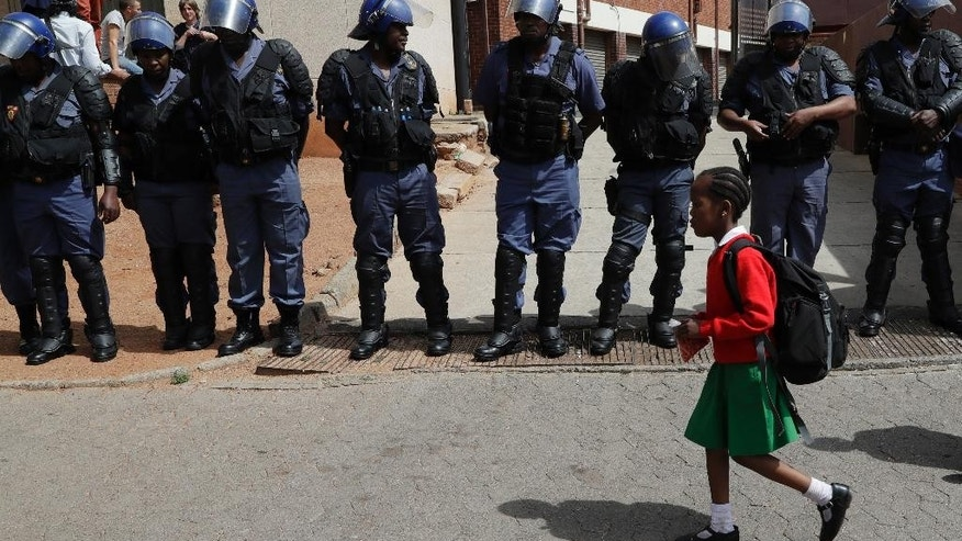 A young girl wearing school uniform, walks past riot police officers as they guard students from the University of the Witswatersrand outside the Hillbrow Magistrate's Court in Johannesburg, South Africa, Wednesday, Oct. 12, 2016, protesting in support of their peers who were arrested earlier this week. (AP Photo/Themba Hadebe)