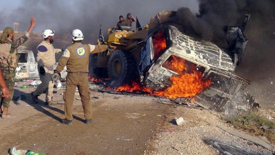 "FILE - This Sept. 1, 2016 file photo provided by the Syria Press Center (SPC), an anti-government media group, shows rescue workers using a bulldozer to remove a burned van after airstrikes that killed a dozen people west of the town of Suran in Hama province, Syria. Infighting among some insurgent groups in Syria is severely hampering an offensive that many activists had hoped would cut government supply lines to Aleppo and ease the pressure on that embattled northern city. A Syrian cabinet minister, Ali Haidar, told The Associated Press in Damascus on Wednesday, Oct. 12, 2016, that Hama was the ""safety valve which the gunmen tried to open to alleviate pressure on Aleppo."" (Syria Press Center via AP, File)"