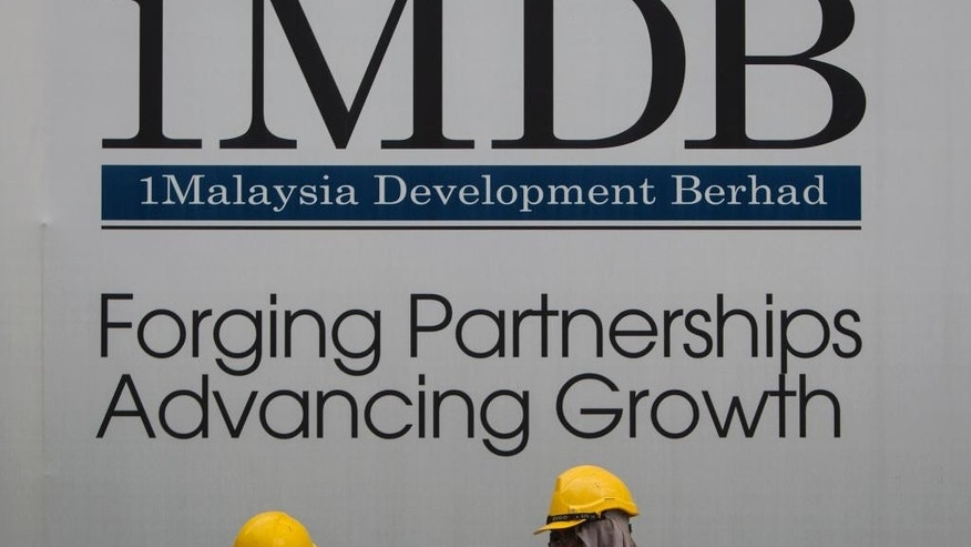 FILE - In this May 14, 2015 file photo, construction workers chat in front of a billboard for state investment fund 1 Malaysia Development Berhad (1MDB) at the fund's flagship Tun Razak Exchange development in Kuala Lumpur, Malaysia. Singapore regulators ordered the closure Tuesday, Oct. 11, 2016 of Falcon Private Bank, citing alleged slack controls for transfers and improper conduct related to 1MDB, an indebted Malaysian state fund. (AP Photo/Joshua Paul, File)