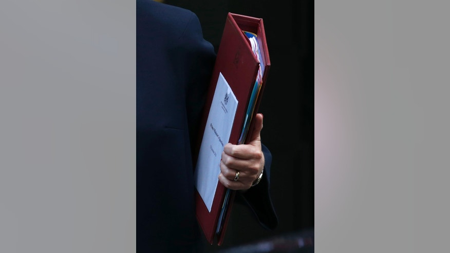 Britain's Prime Minister Theresa May holds onto her notes as she leaves 10 Downing Street for the House of Commons for her weekly Prime Minister's Questions, in London, Wednesday, Oct. 12, 2016. (AP Photo/Alastair Grant)