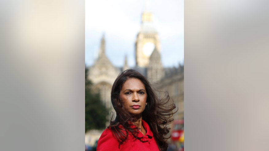 Gina Miller poses for a portrait near the Houses of Parliament in London, Wednesday, Oct. 12, 2016. Financial entrepreneur Gina Miller's landmark lawsuit begins with a simple question: can Theresa May's government invoke Article 50 and trigger the exit from the European Union without an act of Parliament. (AP Photo/Alastair Grant)
