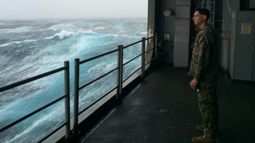 In this Sunday, Oct. 9, 2016 photo, Marine Gunnery Sgt. Jeremiah Benjamin, 34, of San Diego, watches the Atlantic churn aboard the USS Iwo Jima. Benjamin is among a group of Marines and sailors bound for Haiti to help out with relief efforts following Hurricane Matthew's destruction. (AP Photo/Ben Finley)