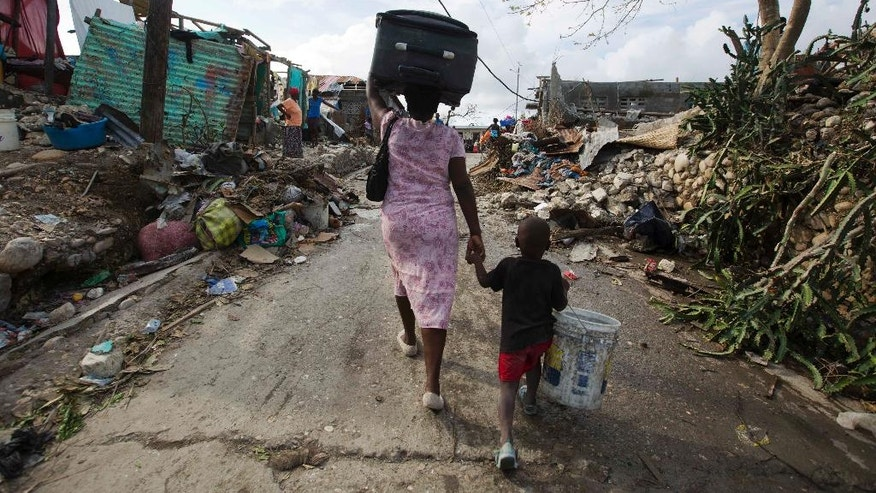 A woman walks to a shelter with her son as they leave after their home was destroyed by Hurricane Matthew in Jeremie, Haiti on Sunday, Oct. 9, 2016. Jeremie appears to be the epicenter of the country's growing humanitarian crisis in the wake of the storm. (AP Photo/Dieu Nalio Chery)