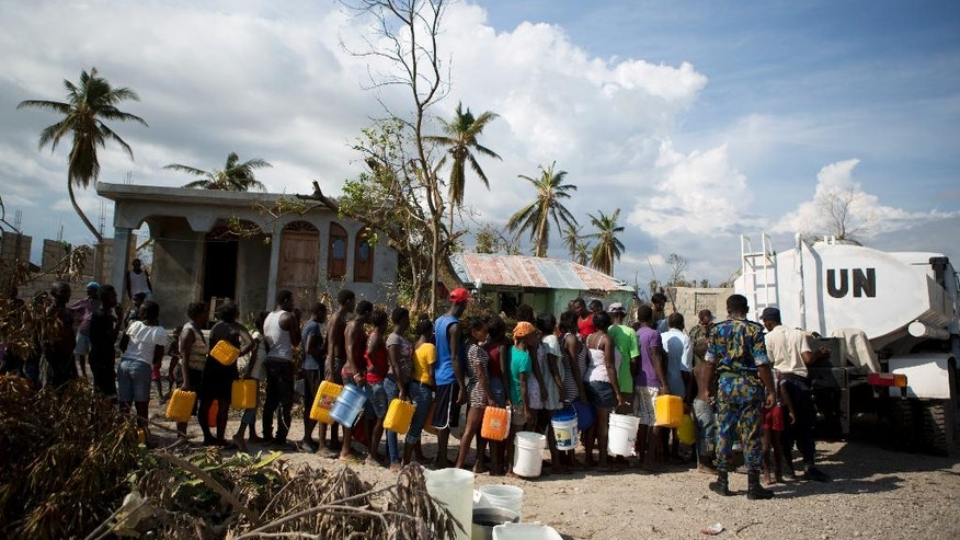 United Nations police from Bangladesh deliver drinking water to residents of Sous-Roche village, outside Les Cayes, Haiti, Tuesday, Oct. 11, 2016. Health authorities have warned that Hurricane Matthew has created conditions that are likely to cause an increase in the deadly waterborne cholera virus.(AP Photo/Rebecca Blackwell)