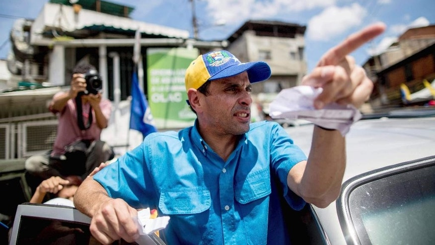 Opposition leader Henrique Capriles gestures to supporters near a voting center gathering to protest the conditions set by electoral authorities for a recall referendum to go forward against Venezuela's President Nicolas Maduro in Caracas, Venezuela, Wednesday, Oct. 12, 2016. The opposition has held a series of marches since a major rally on Sept. 1, and all have drawn underwhelming turnout. (AP Photo/Alejandro Cegarra)