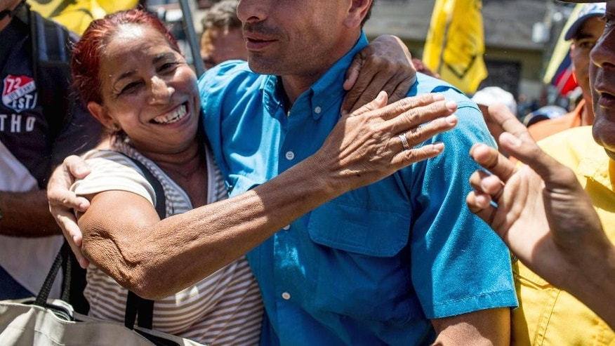 Opposition leader Henrique Capriles is hugged by a supporter during a gathering outside a voting center where they protest the conditions set by electoral authorities for a recall referendum to go forward against Venezuela's President Nicolas Maduro in Caracas, Venezuela, Wednesday, Oct. 12, 2016. The opposition has held a series of marches since a major rally on Sept. 1, and all have drawn underwhelming turnout. (AP Photo/Alejandro Cegarra)