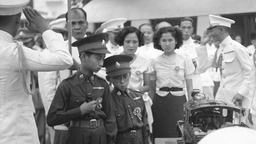 FILE - In this Dec. 16, 1938, file photo, thirteen-year-old King Ananda of Siam, now known as Thailand, left, and his brother Prince Bhumibol, right, inspect a model train presented to him at Saranromya Gardens in Bangkok. Thailand's Royal Palace said on Thursday, Oct. 13, 2016, that Thailand's King Bhumibol Adulyadej, the world's longest-reigning monarch, has died at age 88.  (AP Photo, File)