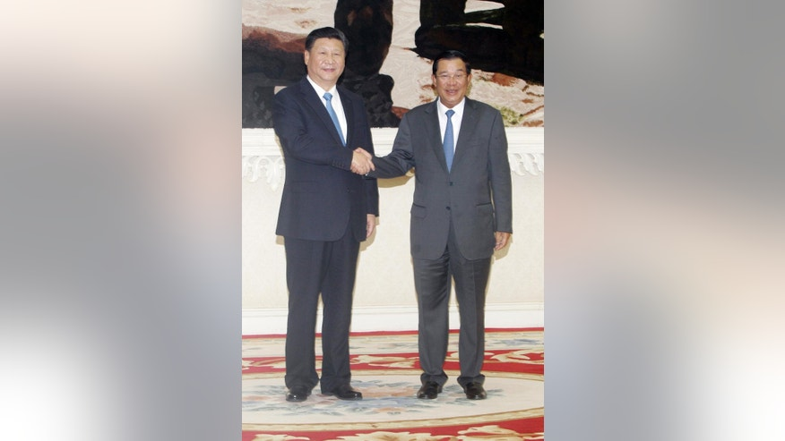 Cambodian Prime Minister Hun Sen, right, shakes hands with  Chinese President Xi Jinping, left, in Phnom Penh, Cambodia, Thursday, Oct. 13, 2016. Xi is on a state visit to strengthen the relationships between the two countries and to witness the agreements to be signed. (AP Photo/Heng Sinith)