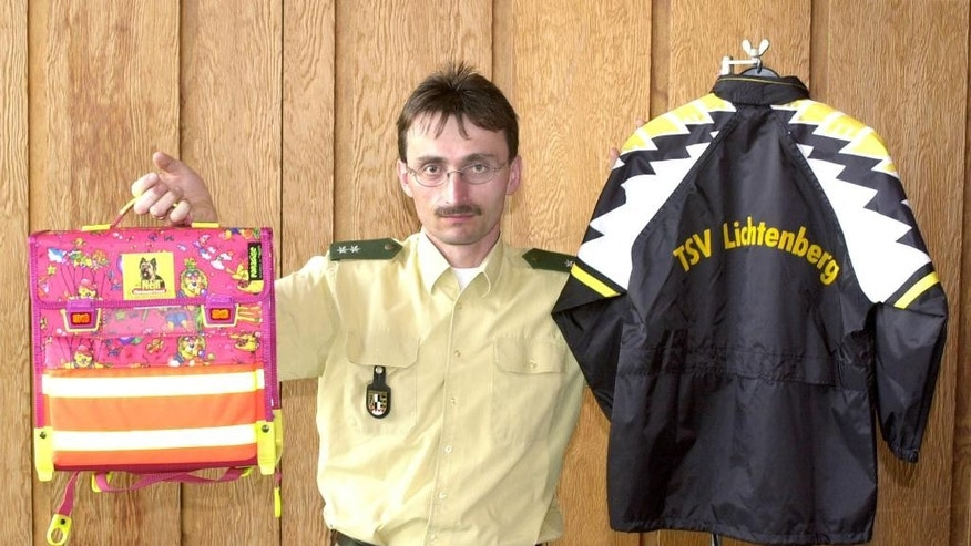 FILE - In this May 11, 2001 file photo Klaus Bernhardt, then spokesperson of the police Hof, shows stuff similar to the a bag and jacket similar to what was worn by nine-year-old Peggy who disappeared in May 2001. Her remains were found in spring 2016.  (AP Photo/Jens Meyer, file)