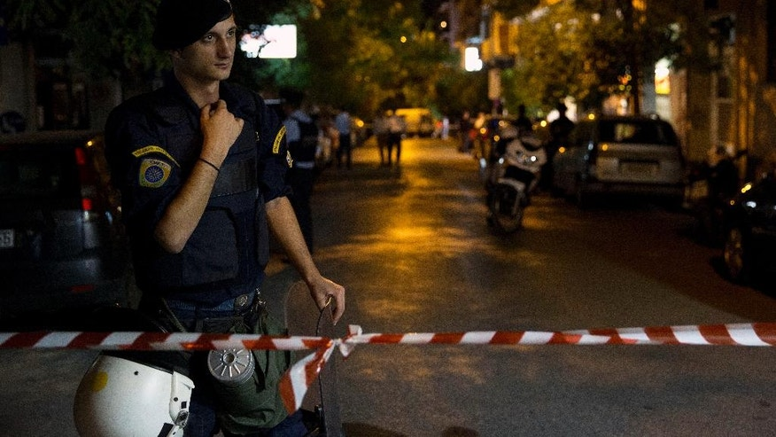 Police tape off the area where a bomb went off in Athens, early Thursday, Oct. 13, 2016. Police in Greece say a bookstore selling survivalist literature in central Athens has been targeted in a bomb attack, causing damage but no injuries.(AP Photo/Petros Giannakouris)