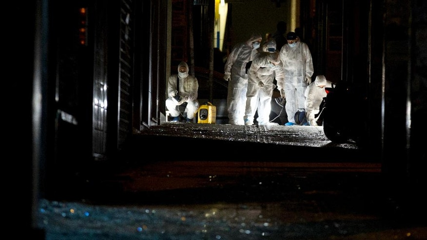 Police forensic expert search a sidewalk for evidence after a bomb explosion, in central Athens, early Thursday, Oct. 13, 2016. Police in Greece say a bookstore selling survivalist literature in Athens has been targeted in a bomb attack, causing damage but no injuries.(AP Photo/Petros Giannakouris)