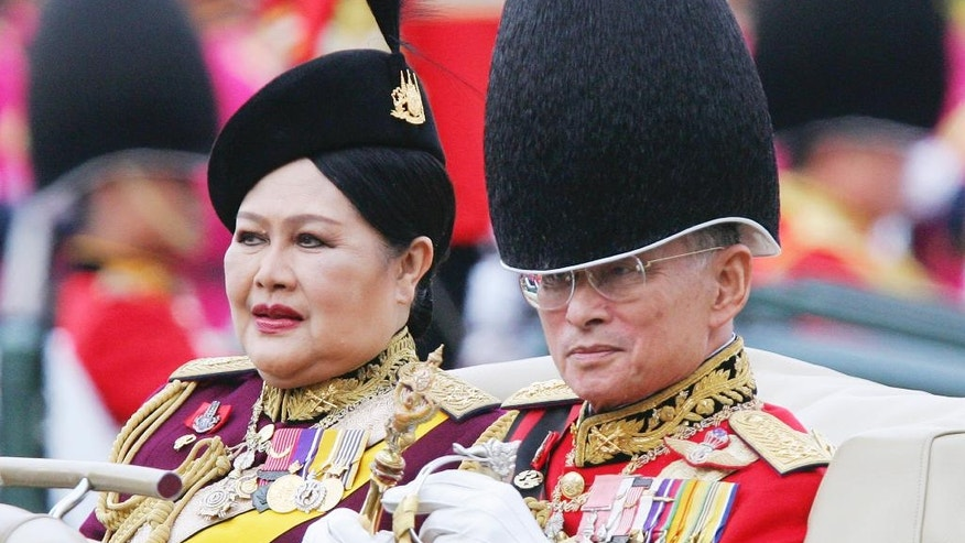 FILE - In this Dec. 2, 2005, file photo,Thailand's King Bhumibol Adulyadej and Queen Sirikit review the honor guard during a ceremony ahead of his 78th birthday in Bangkok. Thailand's Royal Palace said on Thursday, Oct. 13, 2016, that Thailand's King Bhumibol, the world's longest-reigning monarch, has died at age 88.  (AP Photo/Sakchai Lalit, File)