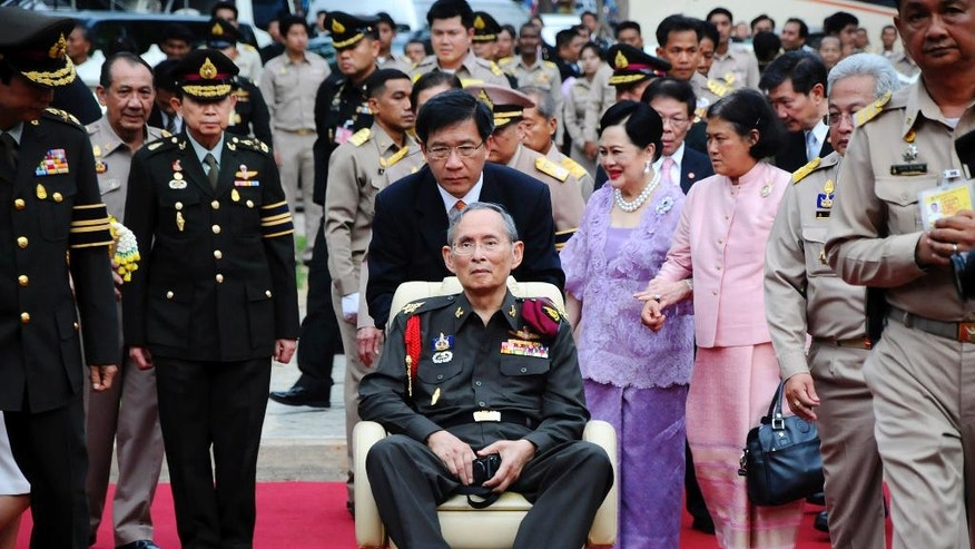 FILE - In this May 25, 2012, file photo, Thailand's King Bhumibol Adulyadej, center, is pushed in a wheelchair as he arrives at a rice field in Ayutthaya province, central Thailand. Thailand's Queen Sirikit, in purple, is walking at rear with Princess Sirindhorn. Thailand's Royal Palace said on Thursday, Oct. 13, 2016, that Thailand's King Bhumibol, the world's longest-reigning monarch, has died at age 88. (AP Photo/File)