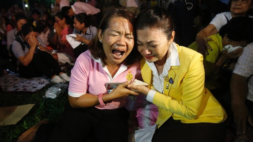 Thais cry outside Siriraj Hospital where King Bhumibol Adulyadej was treated in Bangkok, Thailand, Thursday, Oct. 13, 2016. Thailand's Royal Palace said King Bhumibol, the world's longest-reigning monarch, has died at age 88. (AP Photo/Sakchai Lalit)