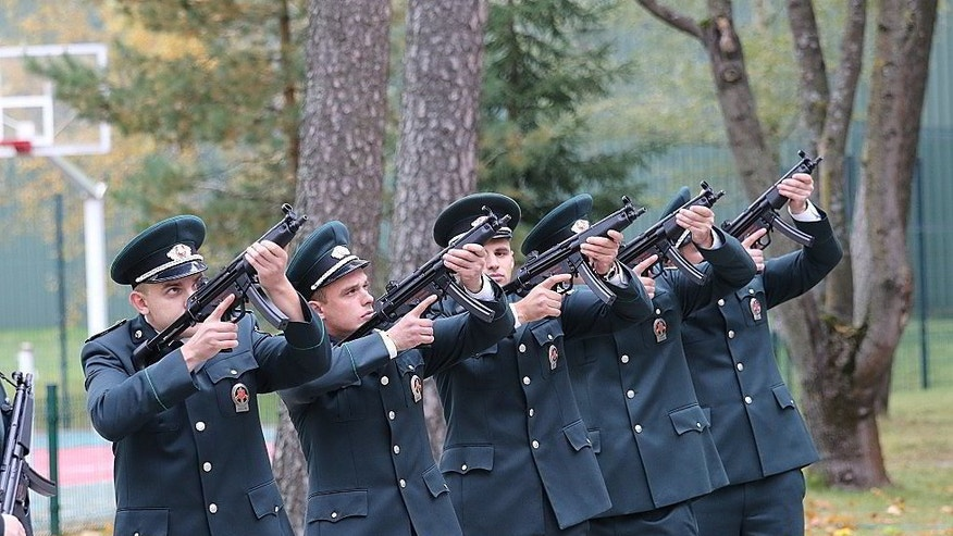 Members of Lithuania's state border guards armed with automatic weapons fire a volley salute during the ceremonial burial of police dog Ramzis in the western town of Pagegiai, Lithuania, Wednesday, Oct. 12, 2016. The three-year old male dog was killed in action on Sept. 27 when state border officers were tracking smugglers near Russian Kaliningrad exclave border. (Rokas Pukinskas/ State Border Guard Service via AP)