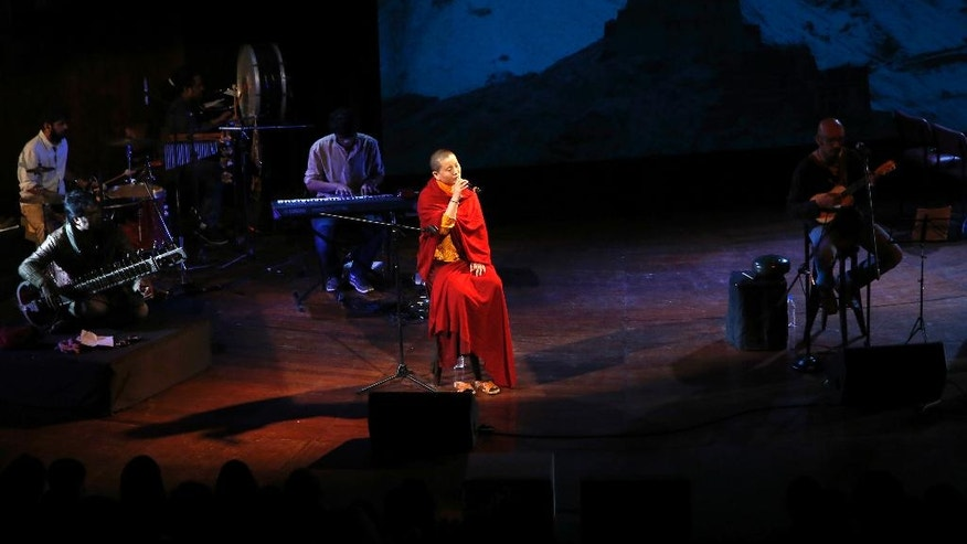 In this Oct. 7, 2016 photo, Buddhist nun and musician Ani Choying Drolma, center, performs during a concert in Mumbai, India. She is one Buddhist nun everyone in Nepal knows by name, not because she's a religious icon and a UNICEF goodwill ambassador, nor for her work running a girl's school and a hospital for kidney patients but because she is one of the country's biggest pop stars. With more than 12 albums of melodious Nepali tunes and Tibetan hymns that highlight themes of peace and harmony, the songstress in saffron robes has won hearts across the Himalayan nation and abroad. (AP Photo/Rajanish Kakade)