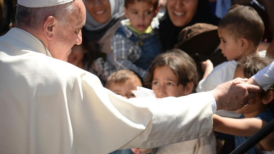 FILE - In this April 16, 2016 file photo, Pope Francis meets refugees at the Moria refugee camp, on the Greek island of Lesbos. The pope, in his annual message for the World Day of Migrants and Refugees on Thursday, Oct. 13, 2016, denounced the forced repatriation of unaccompanied children migrants who flee wars and poverty, saying countries should try to meet their needs rather than return them to uncertain futures back home. (Filippo Monteforte/Pool Photo via AP, File)
