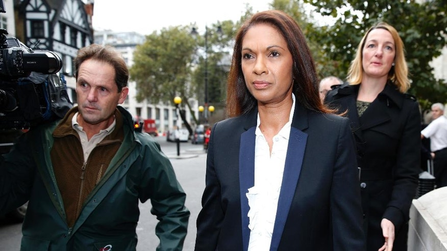 Gina Miller, second from left, walks past the High Court prior to the start of her landmark lawsuit, in London, Thursday, Oct. 13, 2016. Financial entrepreneur Gina Miller's landmark lawsuit begins with a simple question: can Prime Minister Theresa May's government invoke Article 50 and trigger the exit from the European Union without an act of Parliament? (AP Photo/Alastair Grant)