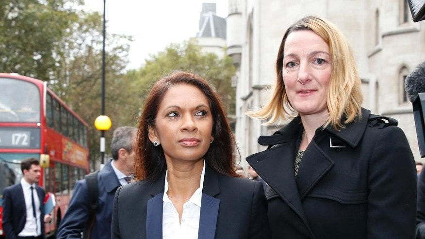 Gina Miller, left, walks past the High Court prior to the start of her landmark lawsuit, in London, Thursday, Oct. 13, 2016. Financial entrepreneur Gina Miller's landmark lawsuit begins with a simple question: can Prime Minister Theresa May's government invoke Article 50 and trigger the exit from the European Union without an act of Parliament? (AP Photo/Alastair Grant)