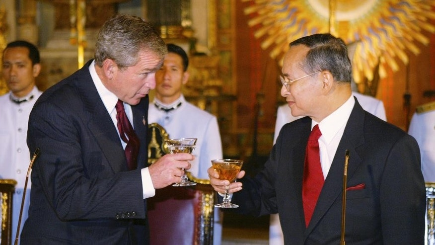 FILE - In this Oct. 19, 2003, file photo, Thailand's King Bhumibol Adulyadej, right, toasts U.S. President George W. Bush, left, at the State Dinner at the Grand Palace in Bangkok. Thailand's Royal Palace said on Thursday, Oct. 13, 2016, that King Bhumibol, the world's longest-reigning monarch, has died at age 88. (AP Photo/Charles Dharapak, File)