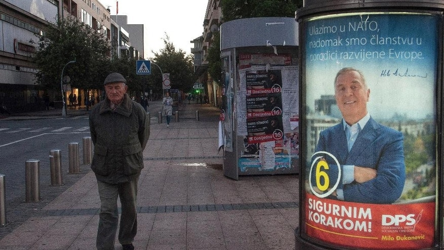 "In this photo taken on Wednesday, Oct. 12, 2016, a man walks by an election poster of pro-Western Prime Minister Milo Djukanovic, leader of the Democratic Party of Socialists, reading ""We are joining NATO, we are at the doorstep at the developed European family"" and ""With firm step ahead!"", in downtown Podgorica, Montenegro. The Sunday general election in the tiny Balkan nation is the most significant since the vote for independence from much larger Serbia a decade ago. (AP Photo/Risto Bozovic)"