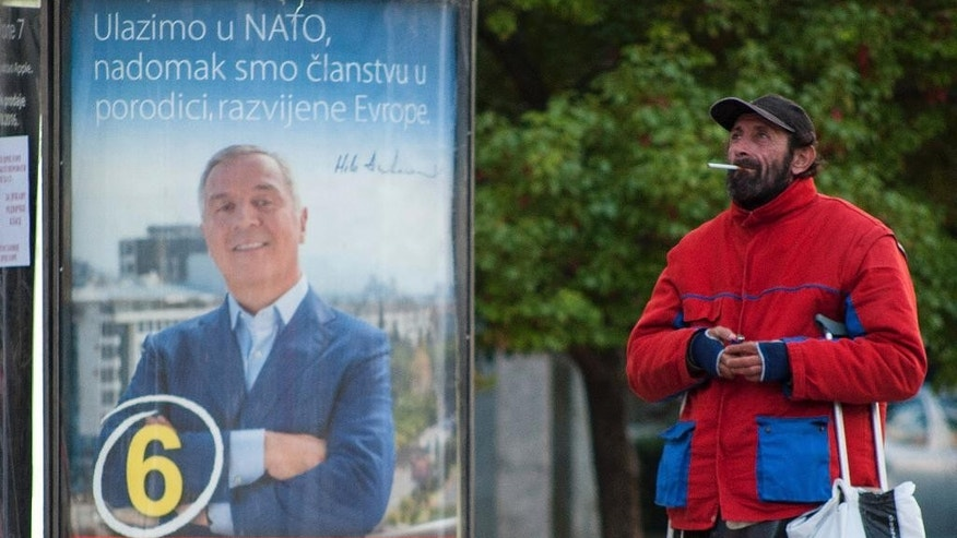 "In this photo taken on Wednesday Oct. 12, 2016, a man walks by an election poster of pro-Western Prime Minister Milo Djukanovic, leader of the Democratic Party of Socialists, reading ""We are joining NATO, we are at the doorstep at the developed European family"" and ""With firm step ahead!"", in downtown Podgorica, Montenegro. The Sunday general election in the tiny Balkan nation is the most significant since the vote for independence from much larger Serbia a decade ago. (AP Photo/Risto Bozovic)"