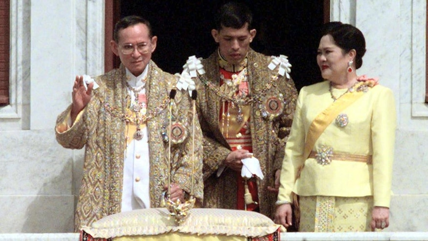 FILE - In this Dec. 5, 1999, file photo,Thailand's King Bhumibol Adulyadej, left, Queen Sirikit, right, and the Crown Prince Maha Vajiralongkorn acknowledge well wishers as they celebrate the King's 72nd birthday. Thailand's Royal Palace said on Thursday, Oct. 13, 2016, that Thailand's King Bhumibol, the world's longest-reigning monarch, has died at age 88.  (AP Photo/Sakchai Lalit, File)